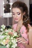 Belle demoiselle d'honneur douce de fille se préparant au mariage d'un ami dans la robe de soirée rose avec la coiffure de soirée Photographie stock