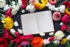 belle disposition de fleurs et carnet vide ouvert Images libres de droits