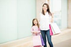 Belle donna e bambina con i sacchetti della spesa immagine stock libera da diritti