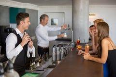 Belle donne che hanno cocktail mentre cameriere che prepara cocktail con l'agitatore di cocktail Immagine Stock Libera da Diritti