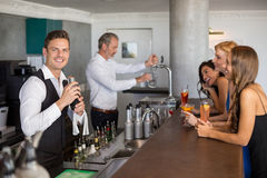 Belle donne che hanno cocktail mentre cameriere che prepara cocktail con l'agitatore di cocktail Fotografia Stock