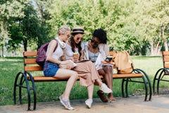 Belle donne che utilizzano compressa mentre riposando sul banco nel parco Fotografie Stock