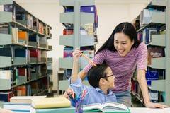 Belle donne con il libro di lettura del ragazzino insieme in biblioteca Immagine Stock