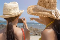 Belle donne del viaggiatore o bello amico che dicono il suo amico di prendere bella foto alla bella spiaggia nella stagione estiv immagine stock libera da diritti