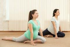 Belle donne incinte che fanno yoga Fotografie Stock Libere da Diritti