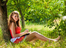Belle donne sorridenti felici che leggono all'aperto Fotografia Stock