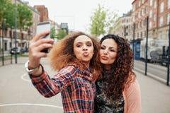 Belle donne sporgenti le labbra che prendono un selfie immagine stock