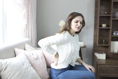 Belle douleur de jeune femme de mal de dos à la maison photos libres de droits