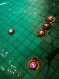 Belle e candele di galleggiamento variopinte nell'acqua dello stagno, nel dettaglio buddista e nel fondo fotografie stock libere da diritti