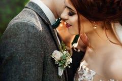 Belle e giovani coppie che stanno insieme vicino al cespuglio verde Fotografia Stock Libera da Diritti