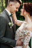 Belle e giovani coppie che stanno insieme vicino al cespuglio verde Immagini Stock Libere da Diritti