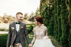 Belle e giovani coppie che stanno insieme vicino al cespuglio verde Fotografie Stock Libere da Diritti