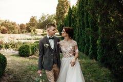 Belle e giovani coppie che stanno insieme vicino al cespuglio verde Fotografia Stock