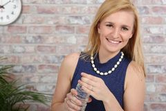 Belle eau potable blonde de femme d'affaires images libres de droits