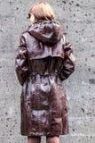 Belle et à la mode jeune femme dans une longue veste de luxe de python de peau de serpent posant près du mur gris photos stock