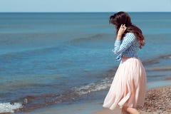 Belle et élégante brune marchant sur la plage photographie stock