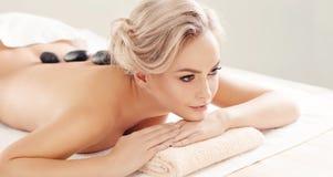 Belle et en bonne santé femme blonde obtenant la thérapie de station thermale et massant des traitements Images libres de droits