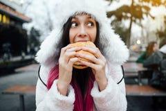 Belle et gaie fille mangeant un hamburger juteux et des pommes frites sur la rue images libres de droits
