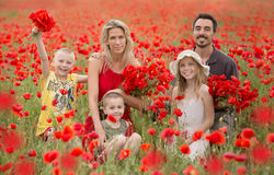 Belle et heureuse famille ensemble, dans un domaine rouge des pavots Photos stock