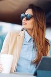 Belle et jeune fille dans des lunettes de soleil buvant du café dans la rue et lisant les actualités dans un comprimé Image stock
