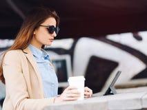 Belle et jeune fille dans des lunettes de soleil buvant du café dans la rue et lisant les actualités dans un comprimé Image libre de droits