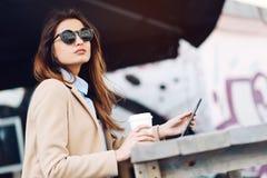 Belle et jeune fille dans des lunettes de soleil buvant du café dans la rue et lisant les actualités dans un comprimé Photographie stock