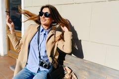 Belle et jeune fille dans un manteau et une écharpe et des lunettes de soleil se reposant sur le banc et les rires Été Le soleil Images stock