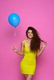 Belle et jeune fille dans une robe jaune tenant un ballon bleu et souriant sur un fond rose Photographie stock