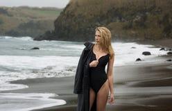 Belle et sexy femme blonde dans le maillot de bain noir avec la veste en cuir à la plage image libre de droits