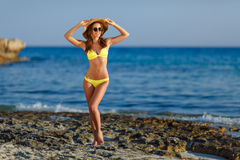 Belle et sexy fille bronzée dans un maillot de bain, un chapeau et un gla jaunes image libre de droits