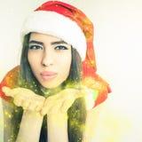 Belle fée latine de femme soufflant le scintillement magique au jour de Noël Images stock