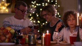 Belle famille à la table de Noël par lueur d'une bougie Vin de grand-mère et première génération de boissons des verres, petit-fi banque de vidéos