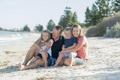 Belle famille caucasienne heureuse ayant des vacances sur la plage souriant avec la mère et le père s'asseyant sur le sable avec  Photographie stock