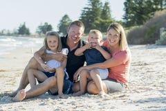 Belle famille caucasienne heureuse ayant des vacances sur la plage souriant avec la mère et le père s'asseyant sur le sable avec  Photos stock