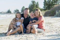 Belle famille caucasienne heureuse ayant des vacances sur la plage souriant avec la mère et le père s'asseyant sur le sable avec  Image stock