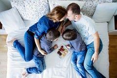 Belle famille de quatre, se trouvant sur le lit, mangeant des fraises Images stock