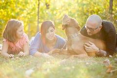 Belle famille de trois magnifique jouant en parc avec le thei Photo stock