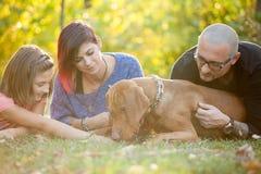Belle famille de trois magnifique jouant en parc avec le thei Image libre de droits
