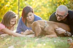Belle famille de trois magnifique jouant en parc avec le thei Images libres de droits