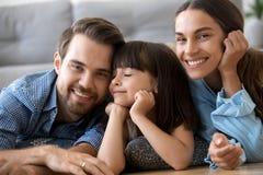 Belle famille diverse se trouvant sur le plancher chaud à la maison image stock