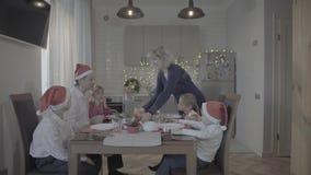 Belle famille enthousiaste heureuse de six dîners de Noël de célébration dans la cuisine confortable de l'atmosphère de fête banque de vidéos