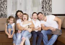 Belle famille gaie riant ensemble à la maison pendant la h Photo libre de droits