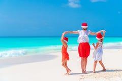 Belle famille heureuse de la mère et des enfants dans des chapeaux rouges de Santa sur une plage tropicale célébrant des vacances Images libres de droits