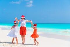 Belle famille heureuse de la maman et des enfants dans des chapeaux rouges de Santa sur une plage tropicale célébrant Noël Photographie stock libre de droits