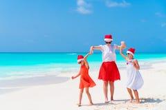 Belle famille heureuse de la maman et des enfants dans des chapeaux rouges de Santa sur une plage tropicale célébrant Noël Image stock