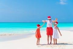 Belle famille heureuse de la maman et des enfants dans des chapeaux rouges de Santa sur une plage tropicale célébrant Noël Images libres de droits