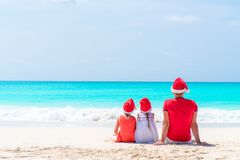 Belle famille heureuse du père et des enfants dans des chapeaux rouges de Santa sur une plage tropicale célébrant des vacances de Photos stock