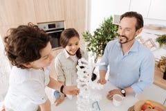 Belle famille mono-parentale étant recueillie autour du modèle d'ADN Image stock