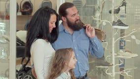 Belle famille regardant l'affichage du magasin d'habillement le centre commercial banque de vidéos