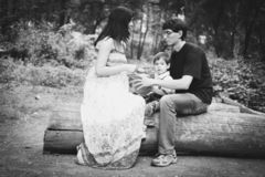Belle famille - une femme heureuse enceinte, un papa riant et un petit fils reposent sur une ouverture la forêt noire et blanche photographie stock